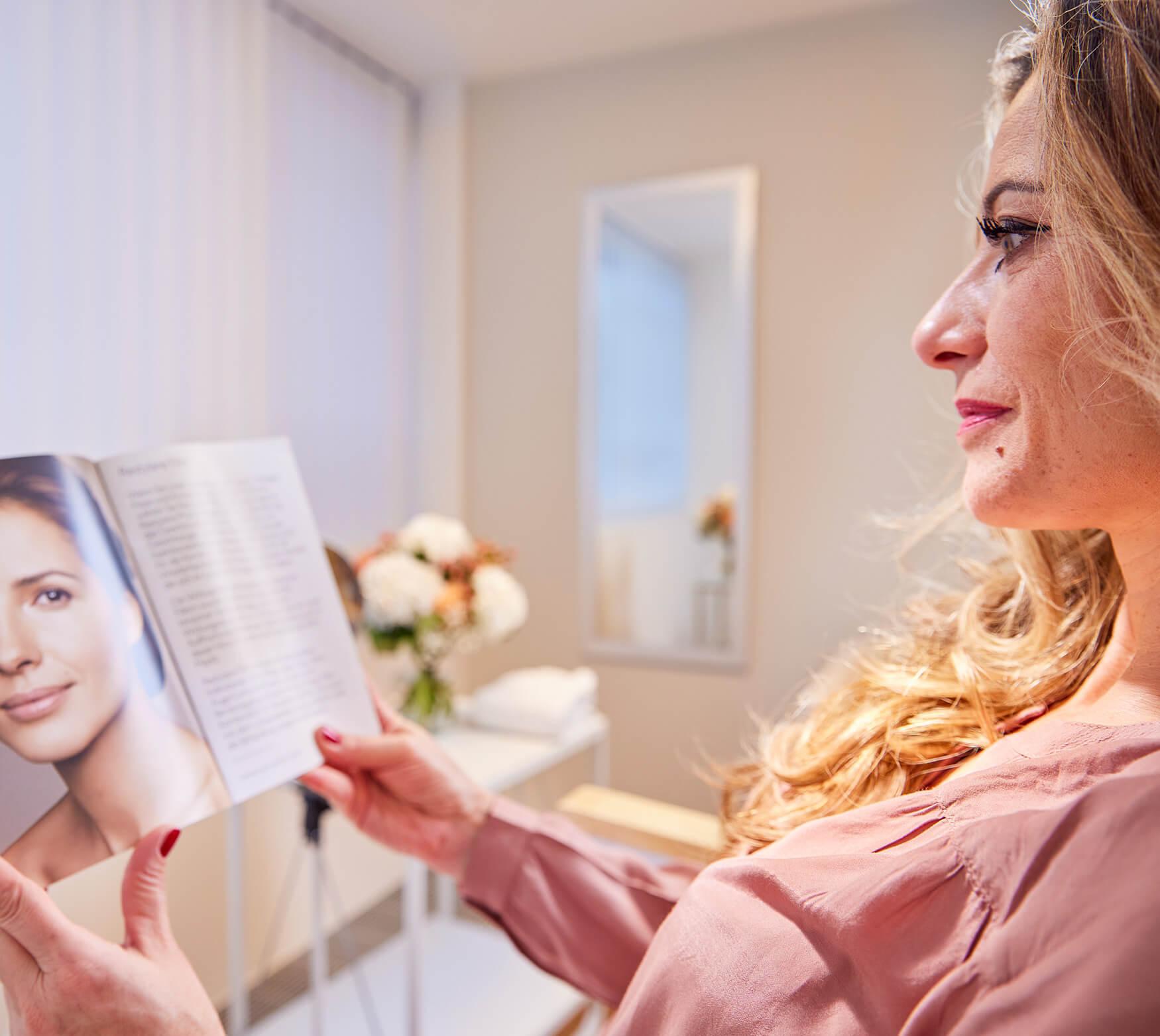 Patientin schaut sich Broschüre zum Thema Filler und Fadenlifting an