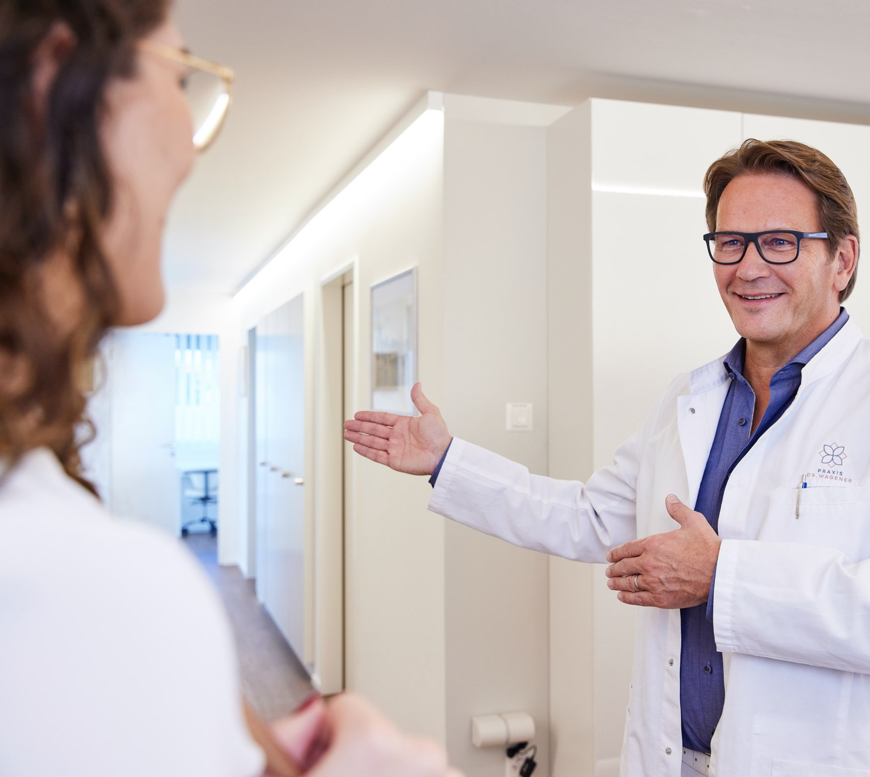 Hausarzt Dr. med. Michael Wagener begrüsst Patientin